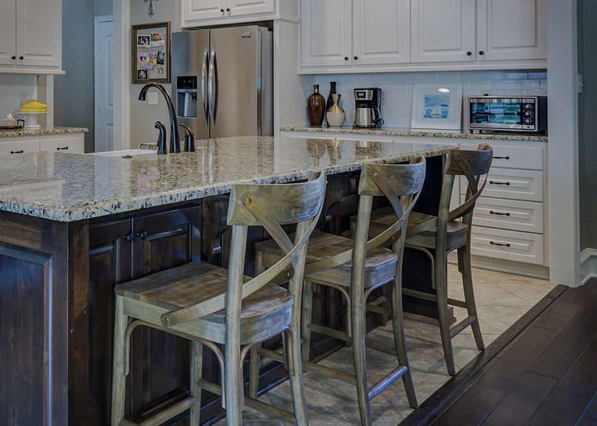 Küchenstühle aus Altholz vermitteln einen schroffen Charakter und setzen Akzente im Raum.